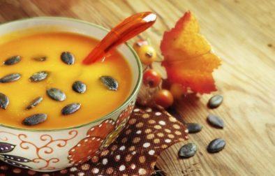 Autumn pumpkin soup with seeps on a wood table
